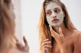 Mum looking in the mirror putting on a clay face mask