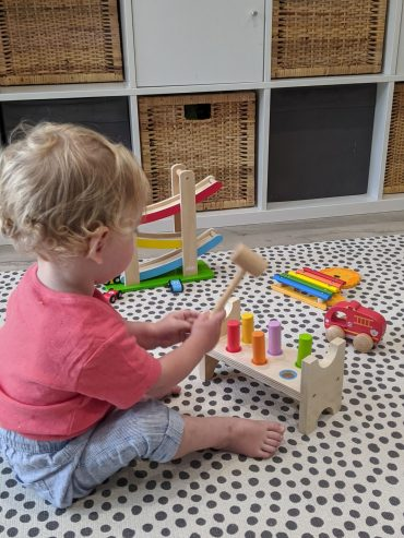 Baby on playmat with wooden hammer banging toys