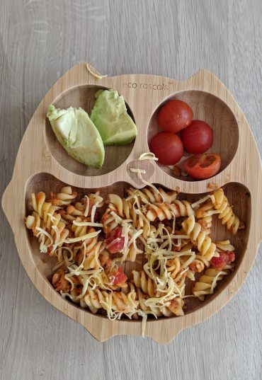 Bamboo owl shaped plate with pasta, avocado and tomatoes